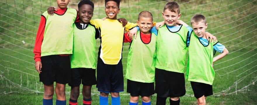 6 kids in green jerseys playing soccer