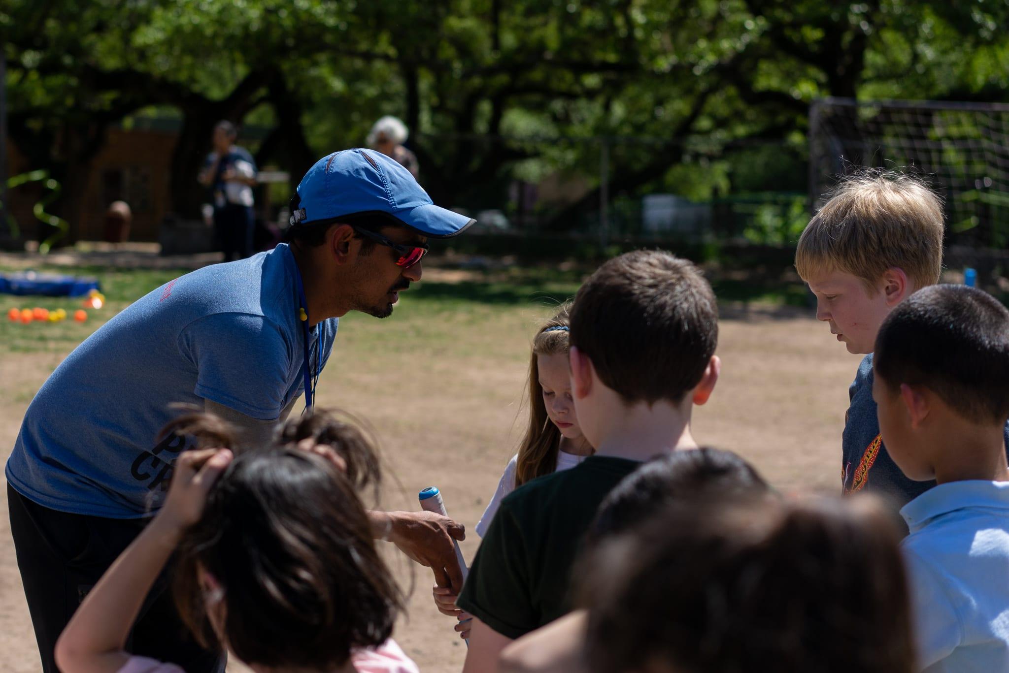 coach explaining cricket to students