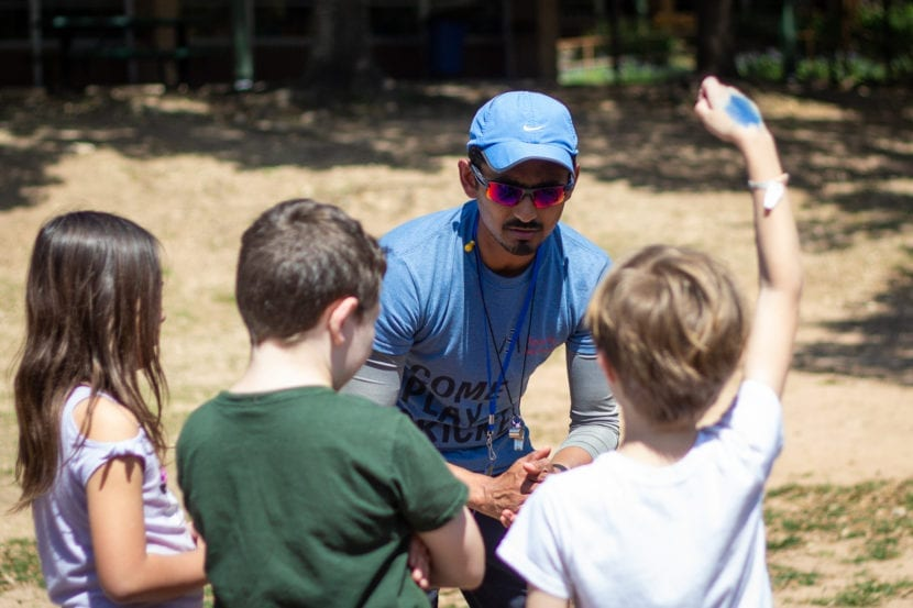 coach talking to three students