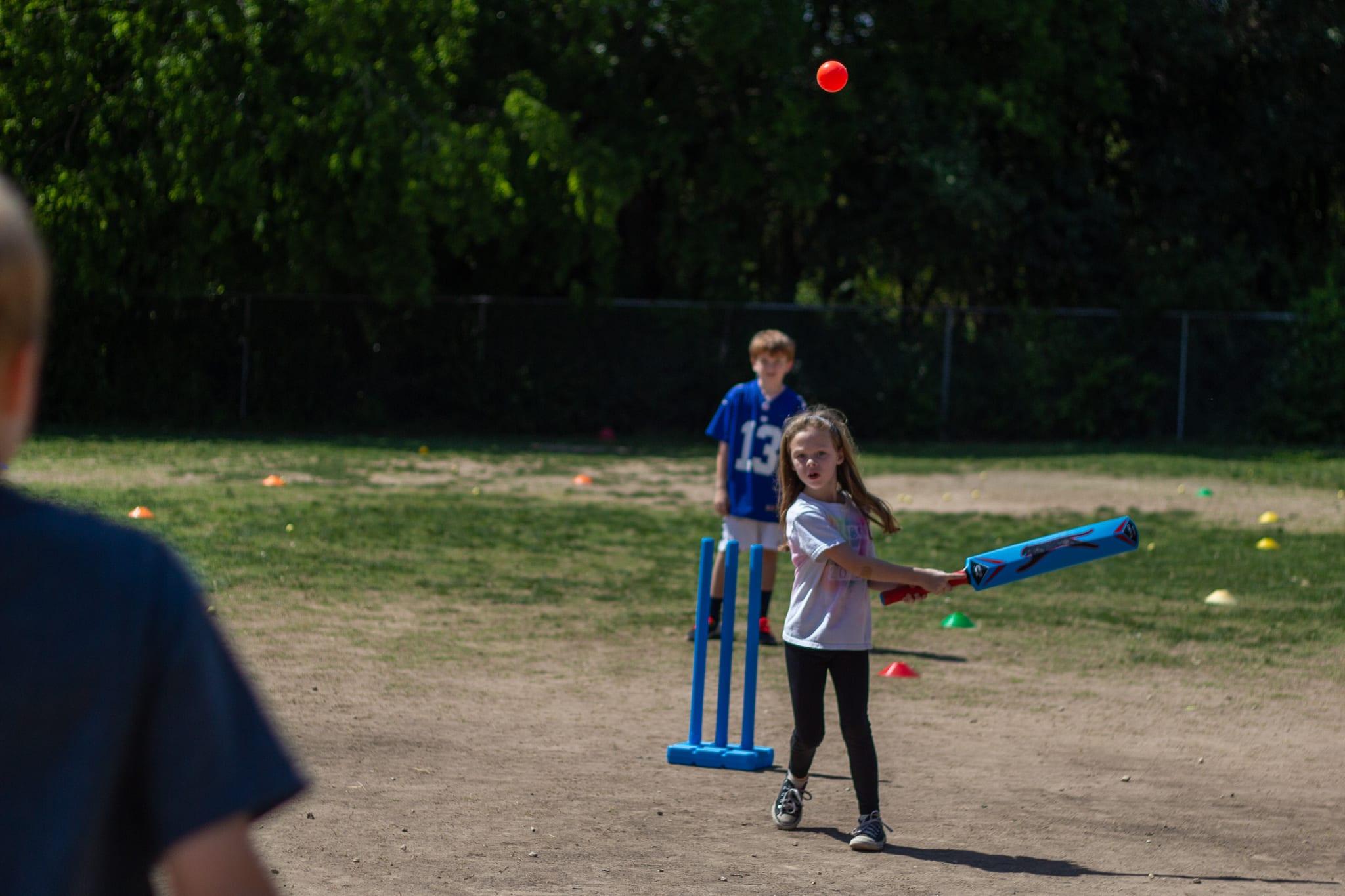 little girl batting cricket ball