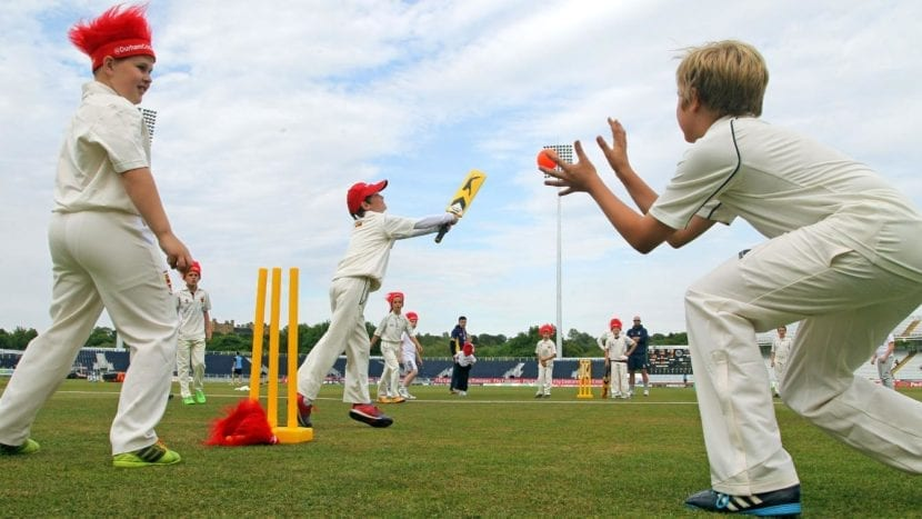 kids in red hats playing cricket