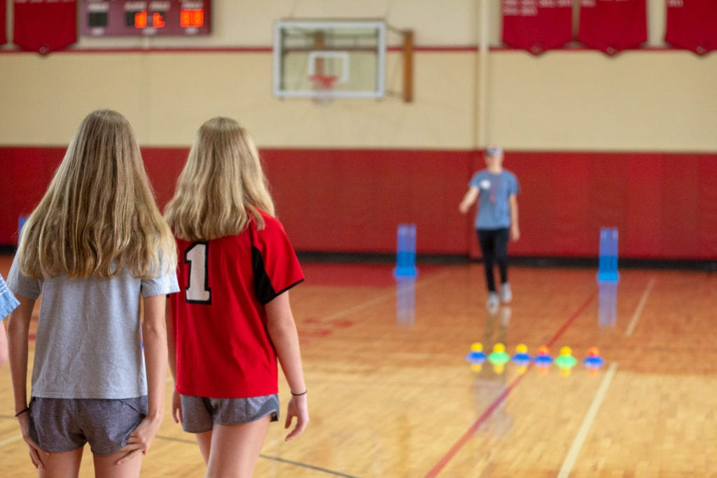 two girls looking at sports movement coach
