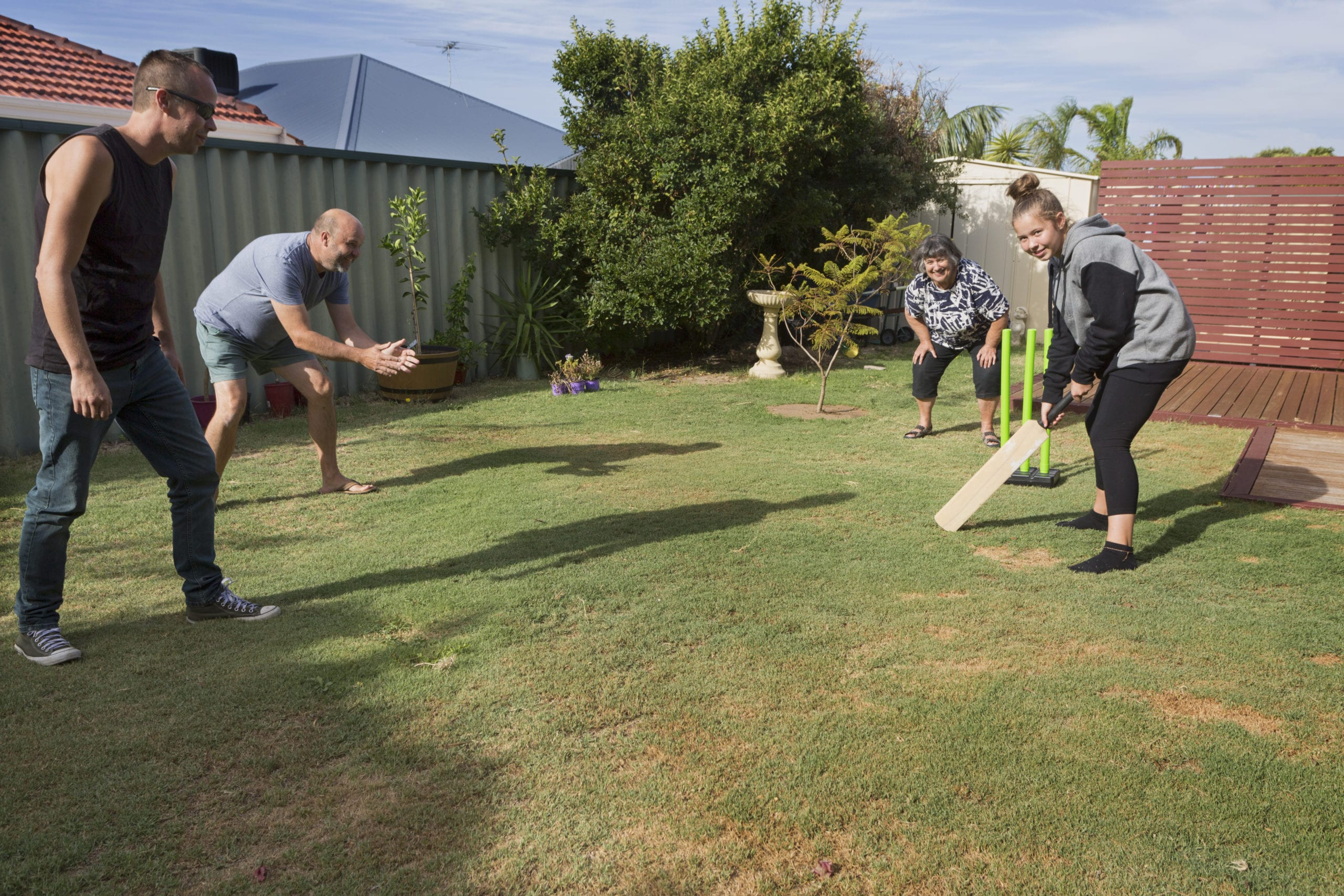 A family playing a traditional game of Back Yard Cricket.