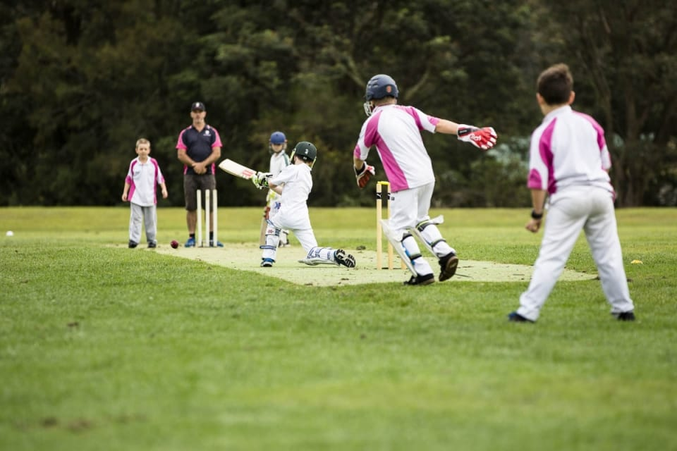 children playing cricket and batting