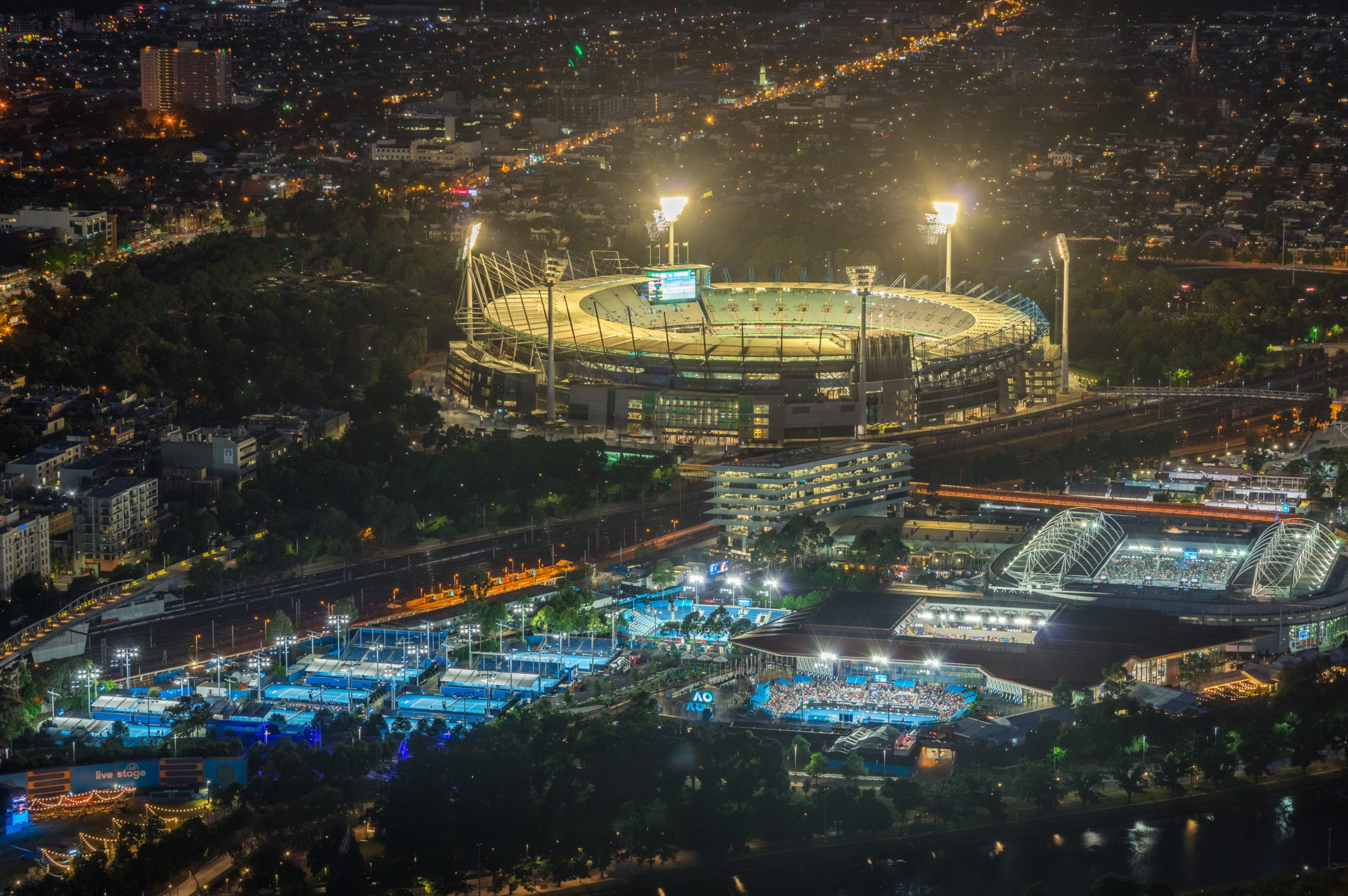 Melbourne Cricket Ground and Yarra Park tennis stadium illuminated at sunset.